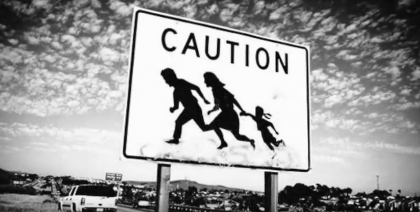 Road sign saying CAUTION with an outline of a family running