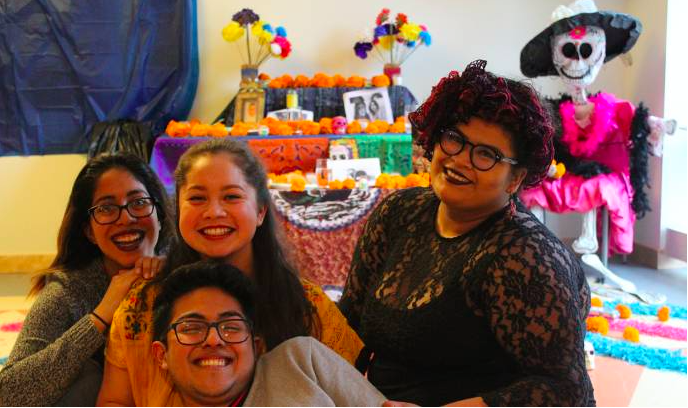 Four friends smiling happily surrounded by colorful Day of the Dead decorations